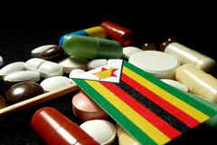 Bandiera dello Zimbabwe con il lotto delle pillole mediche isolate sul nero Fotografia Stock Libera da Diritti