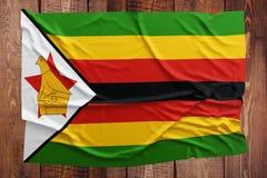 Bandiera dello Zimbabwe su un fondo di legno della tavola Vista superiore corrugata della bandiera dello Zimbabwe immagini stock