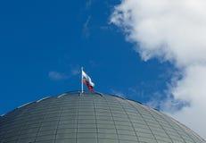 Bandiera di Federazione Russa contro cielo blu sulla cupola della costruzione di astronomia Fotografie Stock