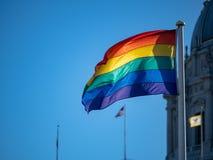 Bandiera di gay pride che ondeggia in aria con la bandiera degli Stati Uniti in backgrou immagine stock libera da diritti