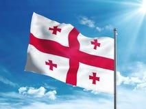 Bandiera di Georgia che ondeggia nel cielo blu Immagini Stock Libere da Diritti
