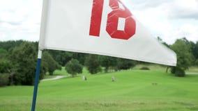 Bandiera di golf che ondeggia un giorno ventoso soleggiato luminoso con il cielo nuvoloso Foro numero 18 della bandiera bianca Pa stock footage
