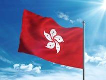 Bandiera di Hong Kong che ondeggia nel cielo blu Immagine Stock