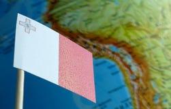 Bandiera di Malta con una mappa del globo come fondo Fotografia Stock