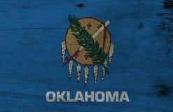 Bandiera di Oklahoma sul fondo di legno del piatto Struttura della bandiera di Oklahoma di lerciume, gli stati dell'America illustrazione di stock