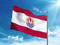 Bandiera di Polinesia francese che ondeggia nel cielo blu Fotografia Stock