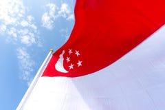 Bandiera di Singapore soffiata sull'asta della bandiera sopra il cielo blu Fotografia Stock Libera da Diritti