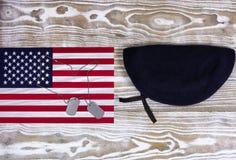 Bandiera di U.S.A. con il berretto militare su fondo di legno bianco sbiadito Fotografie Stock