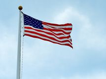 Bandiera di U.S.A. con il fondo delle nuvole e del cielo blu Immagini Stock