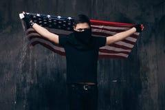 Bandiera di U.S.A. di volo e gangster irriconoscibile Fotografie Stock Libere da Diritti