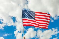 Bandiera di U.S.A. su un'asta della bandiera con le nuvole su fondo Fotografia Stock