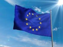 Bandiera di Unione Europea che ondeggia in cielo blu con il sole Fotografia Stock