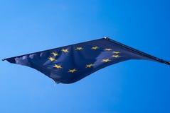 Bandiera di Unione Europea che ondeggia davanti al cielo blu immagine stock