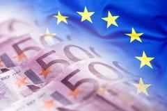 Bandiera di Unione Europea d'ondeggiamento variopinta su un euro fondo dei soldi fotografie stock libere da diritti