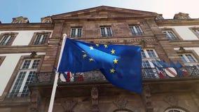 Bandiera di Unione Europea di salto del vento sull'albero contro il fondo del cielo blu davanti a HÃ'tel de Ville de Strasbourg,  video d archivio