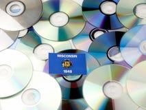 Bandiera di Wisconsin sopra il mucchio di DVD e del CD isolato su bianco Immagini Stock Libere da Diritti