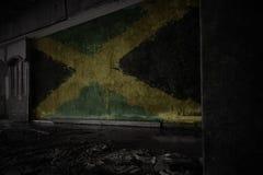 Bandiera dipinta della Giamaica sulla vecchia parete sporca in una casa rovinata abbandonata fotografie stock
