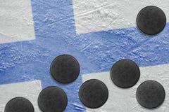 Bandiera e rondelle finlandesi sul ghiaccio Fotografia Stock Libera da Diritti