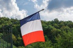 Bandiera francese che ondeggia in vento sulla collina e sul cielo verdi della foresta con il fondo delle nuvole fotografia stock libera da diritti