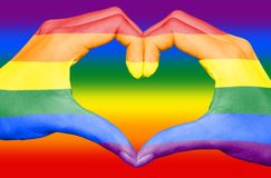 Bandiera gay dell'arcobaleno dipinta sulle mani che formano un cuore sul fondo dell'arcobaleno, concetto gay di amore fotografia stock libera da diritti
