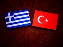 Bandiera greca con la bandiera del turco su un ceppo di albero fotografia stock libera da diritti