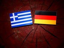 Bandiera greca con la bandiera tedesca su un ceppo di albero immagine stock