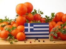 Bandiera greca su un pannello di legno con i pomodori isolati su una b bianca immagini stock libere da diritti