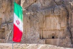 Bandiera iraniana con la necropoli antica Naqsh-e Rustam nella provincia di Fars, Iran nel fondo fotografie stock