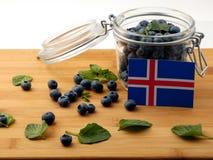 Bandiera islandese su una plancia di legno con i mirtilli su wh fotografia stock