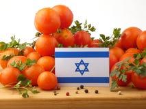 Bandiera israeliana su un pannello di legno con i pomodori isolati su un bianco immagine stock