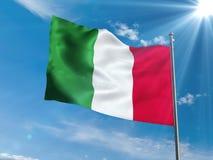 Bandiera italiana che ondeggia in cielo blu con il sole Immagini Stock