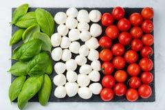 Bandiera italiana fatta con la mozzarella ed il basilico del pomodoro Il concetto di cucina italiana Vista superiore Disposizione fotografie stock