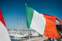 Bandiera italiana sopra parcheggio dell'yacht nel porto Immagini Stock