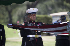 Bandiera marina di piegatura a cerimonia commemorativa per il soldato caduto degli Stati Uniti, PFC Zach Suarez, missione di onor Immagine Stock