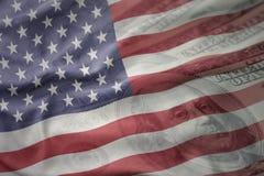 Bandiera nazionale d'ondeggiamento degli Stati Uniti d'America su un fondo americano dei soldi del dollaro Concetto di finanze Fotografia Stock