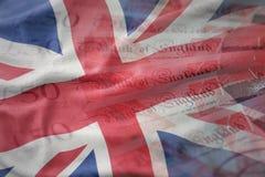bandiera nazionale d'ondeggiamento della Gran Bretagna su un fondo delle banconote dei soldi delle libbre Concetto di finanze Fotografia Stock Libera da Diritti