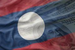 Bandiera nazionale d'ondeggiamento variopinta del Laos su un fondo americano dei soldi del dollaro Immagini Stock