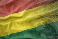 Bandiera nazionale d'ondeggiamento variopinta della Bolivia su un fondo dei soldi del dollaro Concetto di finanze Immagini Stock