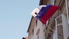 Bandiera nazionale della repubblica della Slovenia contro il sole ed il cielo blu che ondeggiano fuori di un appartamento Rallent archivi video