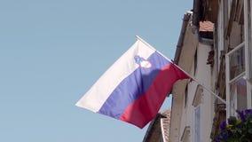 Bandiera nazionale della repubblica della Slovenia contro il sole ed il cielo blu che ondeggiano fuori di un appartamento Rallent video d archivio