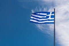 Bandiera nazionale greca che ondeggia sul vento contro il cielo blu ed il briciolo immagine stock libera da diritti