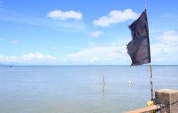 Bandiera nera con il mare del cielo blu Fotografie Stock