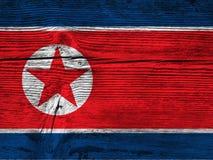 Bandiera nordcoreana sul bordo di legno fotografia stock