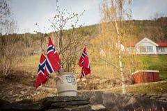Bandiera norvegese con il fondo verde del paesaggio della foresta Simbolo della Norvegia Fotografia Stock