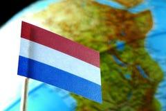 Bandiera olandese con una mappa del globo come fondo Fotografia Stock