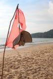 Bandiera rossa del tessuto alla spiaggia Immagine Stock