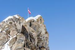 bandiera su roccia e su cielo blu Immagine Stock