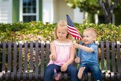Bandiere americane bionde di Comparing Each Others del fratello del bambino e della sorella Fotografia Stock
