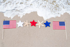 Bandiere americane con le stelle marine sulla spiaggia sabbiosa Immagine Stock