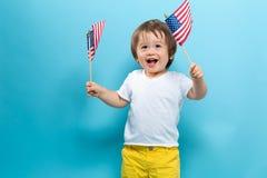 Bandiere americane d'ondeggiamento del ragazzo felice del bambino fotografia stock